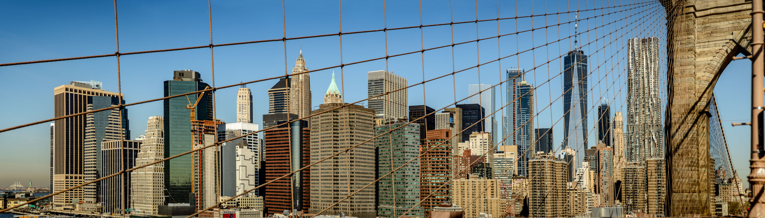 Cool lines formed by stringer cables on Brooklyn Bridge with view of Manhattan.